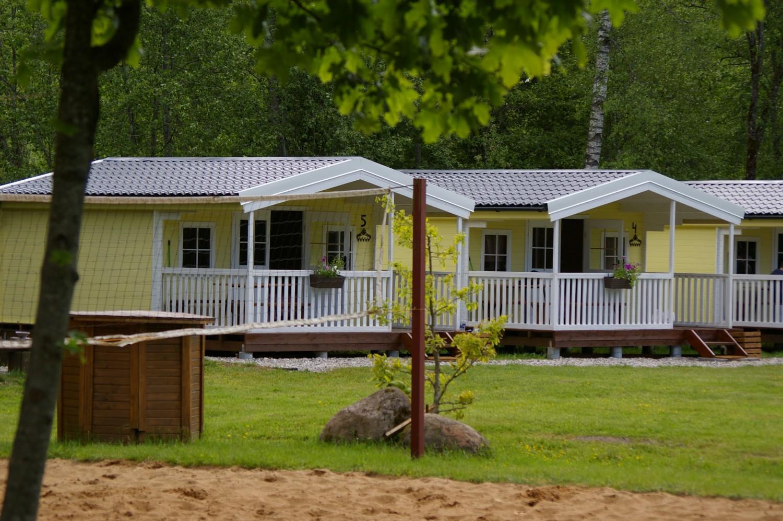 Dobilu slenis stovyklaviete su nameliais prie juros upes, turistauk.lt.